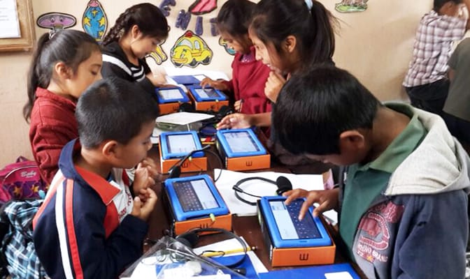 Young boys and girls access offline learning materials on tablets provided by Google and Learning Equality.