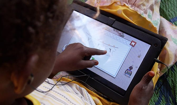 A child plays an educational game on a tablet provided by Google and War Child.