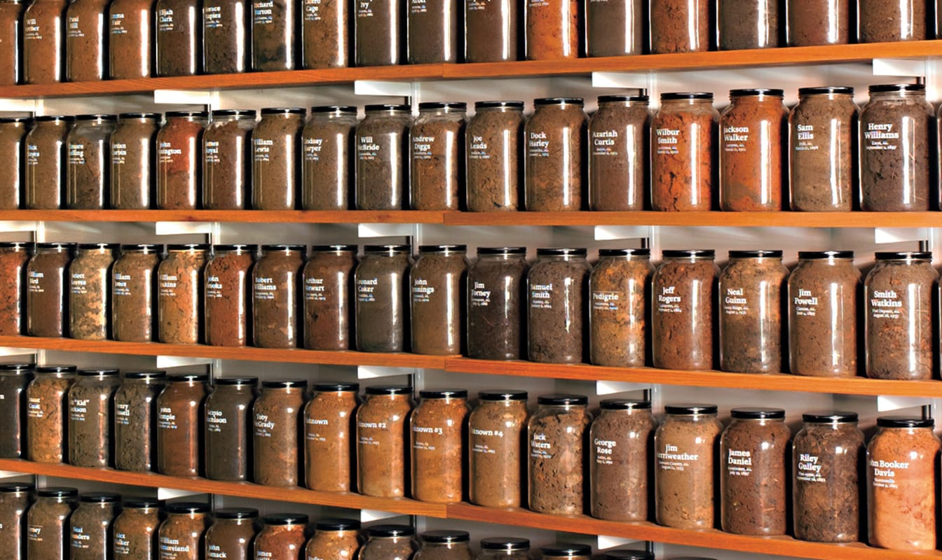 Exhibit commemorating victims of racial injustice, in which jars full of soil from Alabama lynching sites are arranged on shelves