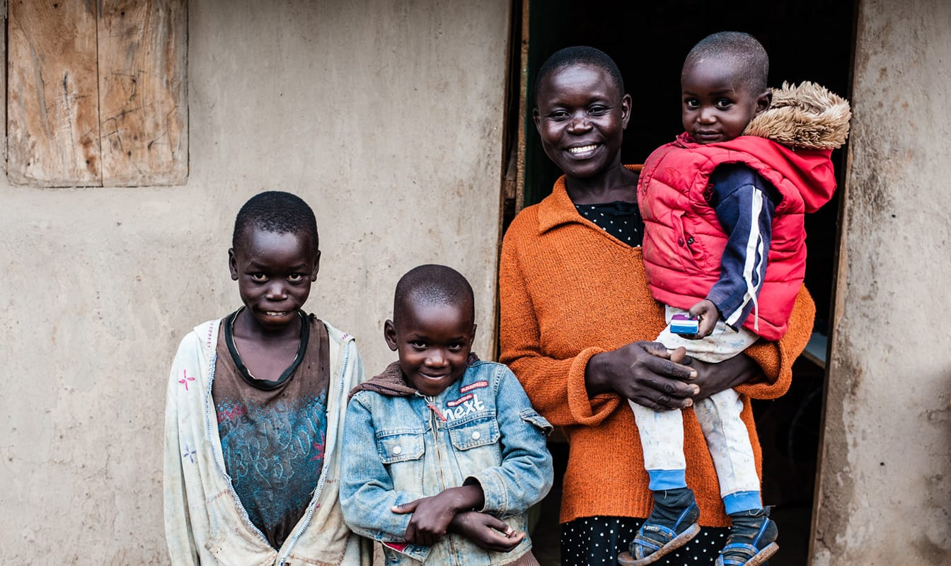 A mother and three children, recipients of GiveDirectly funding, smile in front of their home.