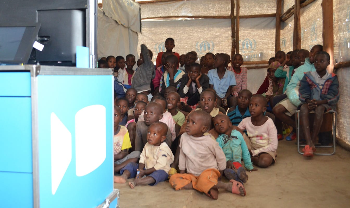 A large group of refugee children watches a television that is placed on top of an Ideas Box.
