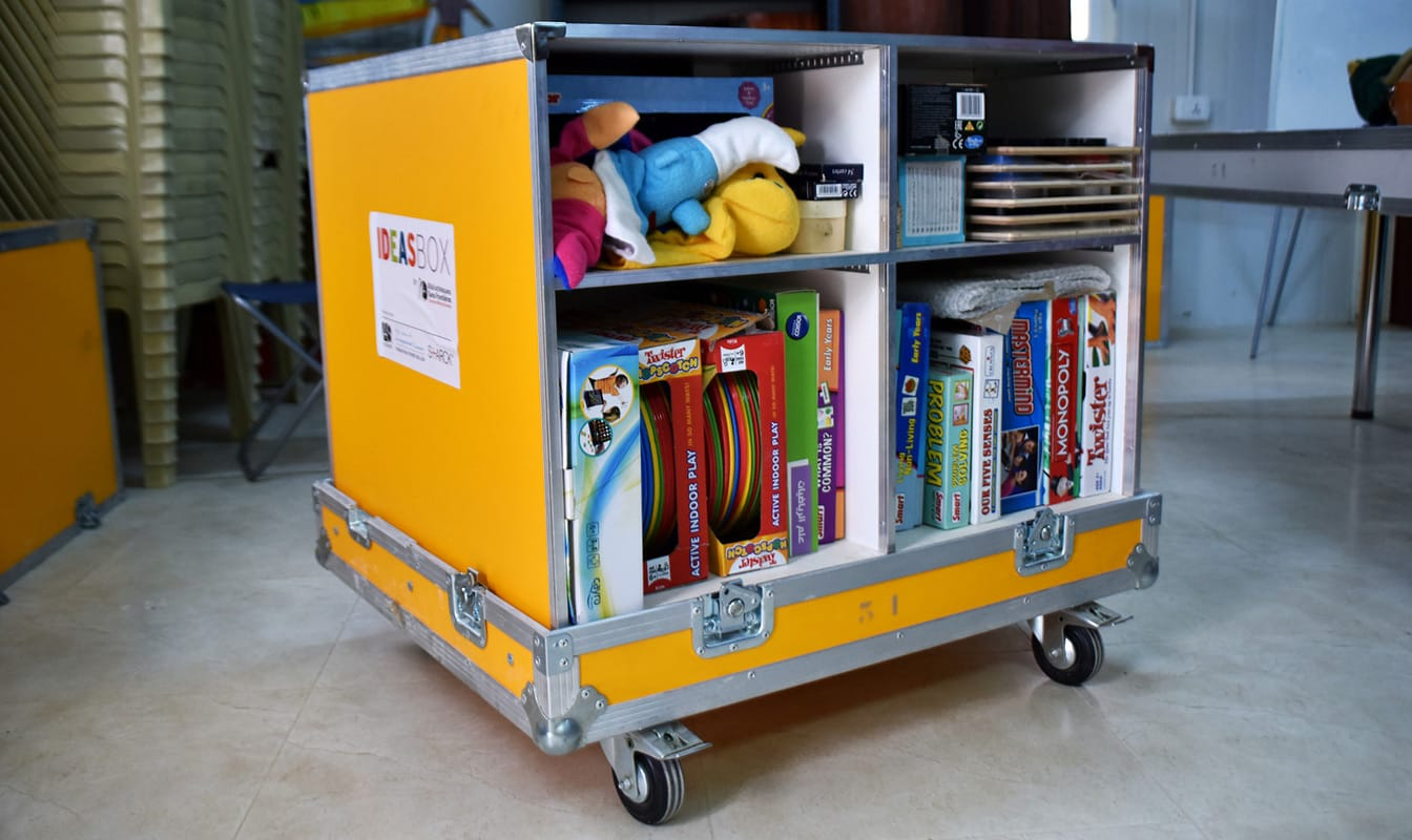 An Ideas Box containing toys, games, and educational materials sits open inside a classroom.
