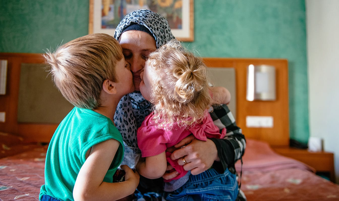 A Mercy Corps field worker embraces two refugee children.
