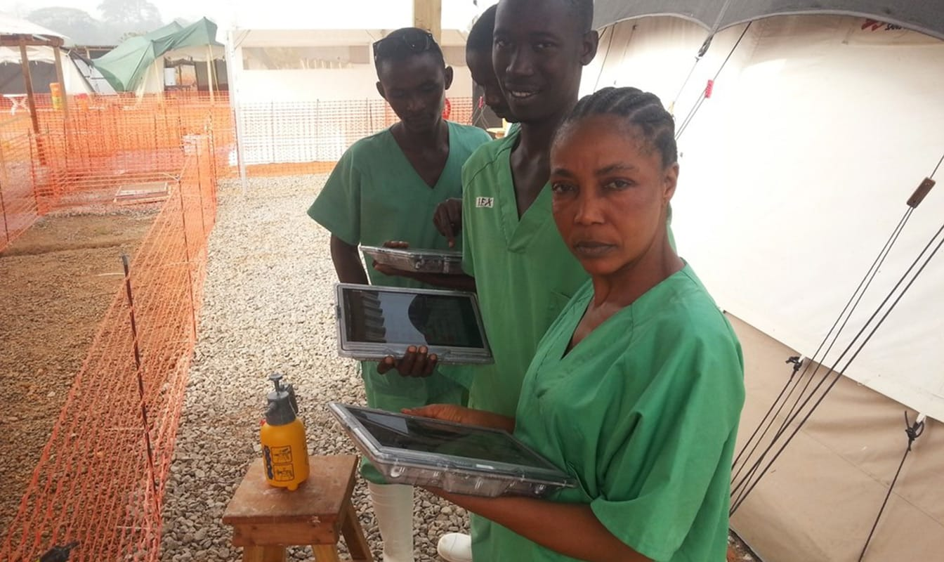 Four MSF field workers look into the camera while using their tablets to access the Project Buendia app.