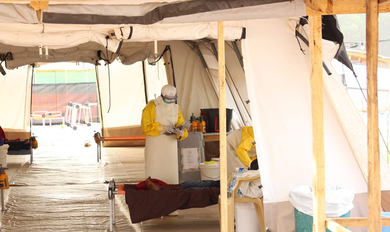An MSF field worker in a medical tent tends to a sick patient, while another uses a tablet to access Project Buendia.