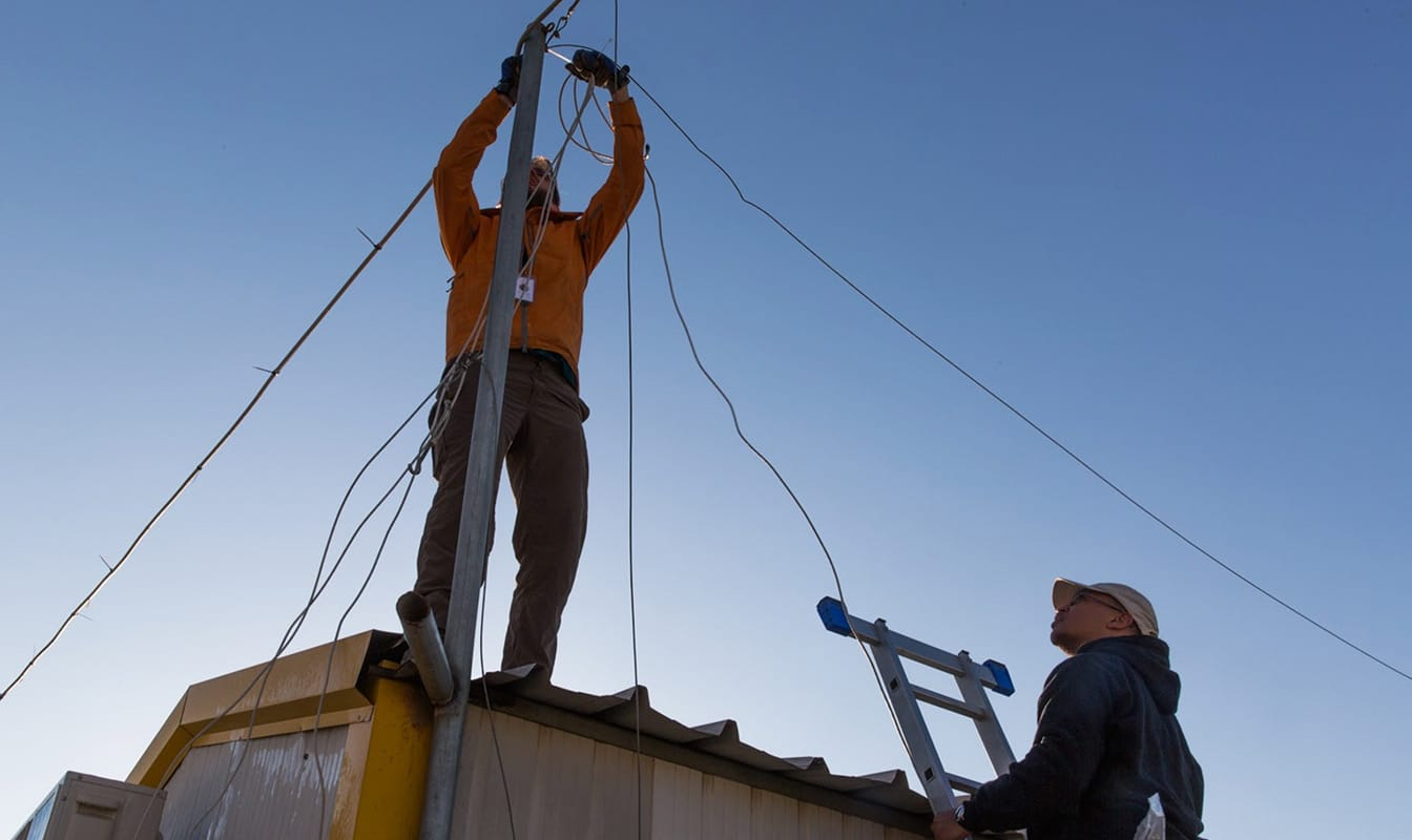 Two NetHope field workers install a WiFi hotspot atop a refugee shelter.