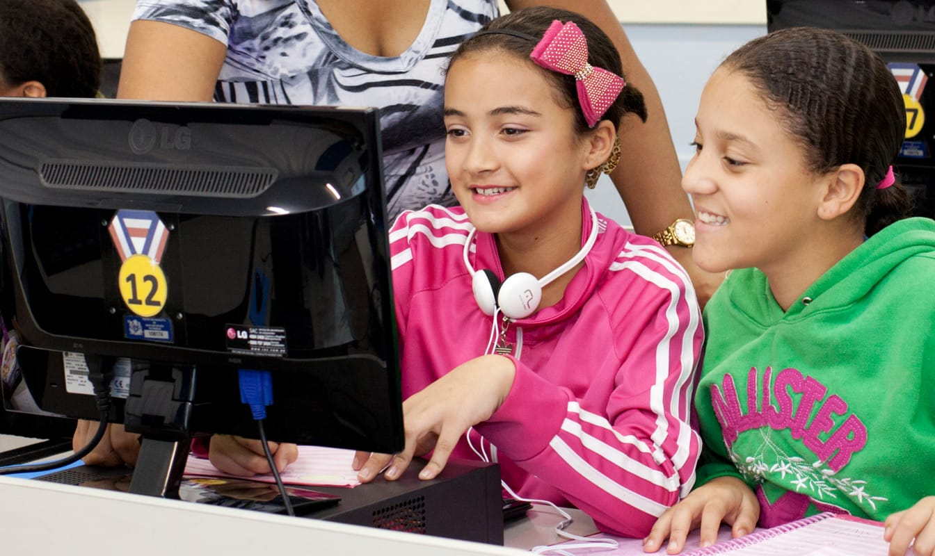 Two Brazilian youths and an instructor look at a computer during a digital lesson.