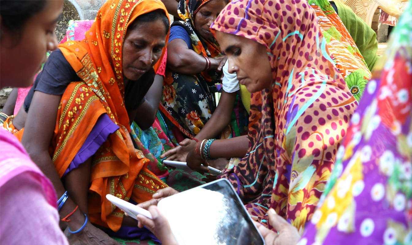 A group of Indian women use tablets supplied by Google and the Pratham Foundation.