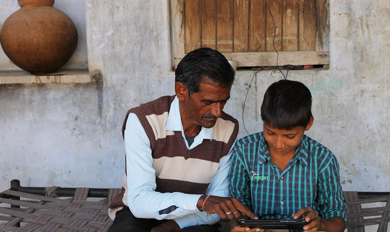 Parent and child access an offline lesson on a tablet.