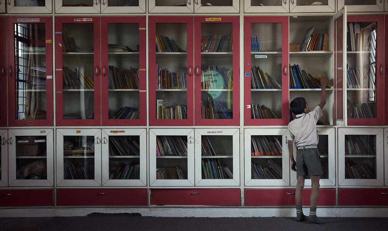 A young boy stands in front a classroom bookshelf, reaching for a book.